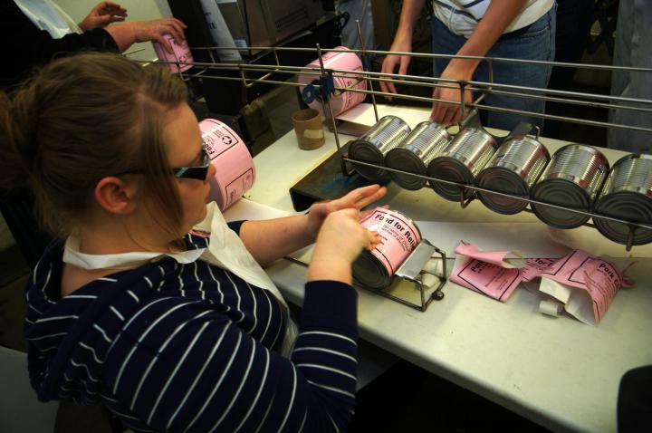 Step 8: Volunteers apply a label to the finished cans indicating what kind of meat is inside.