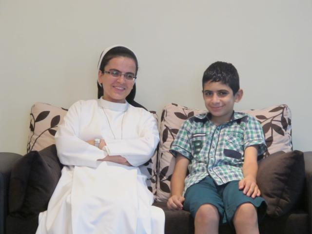 Sister Angela and Bhnam (last name withheld for privacy reasons) from St. Anne's Orphanage in Alqosh, Iraq, relax on a couch at the Daughters of Mary covenant inAnkawa, Iraq. On Aug. 6, 2014, six children and staff remaining in the orphanage fled fromAlqoshbecause of advancing forces fromthe Islamic State group. Normally a two hour trip, it took seven hours of checkpoints and clogged roads. St. Anne's Orphanage is supported by MCC.