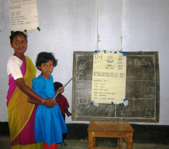 In Bangladesh, preschool teacherCostantinaMandrihelpsMoumitaTuduwith a literacy activity. Although Bengali is the national language in Bangladesh, there are some 45 different indigenous language groups. More than half of children from these groups drop out of primary school, often because of language barriers.MCCsupports preschools that begin instruction in children's own languages and gradually introduce Bengali over a two-year period.