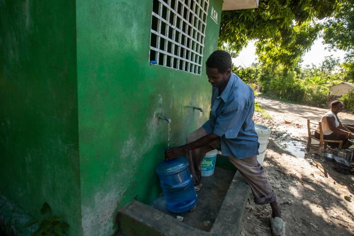 GermainIsaac fills a jug with clean water inDesarmes, a rural town in theArtiboniteValley, the centre of Haiti's cholera outbreak. In response to the threat of cholera,MCCbuilt 32 kiosks and 11 fountains, drawing water from springs in the mountains to town. A local water committee manages each kiosk or fountain. Families using the water pay a small monthly fee, which the committee can use for repairs.