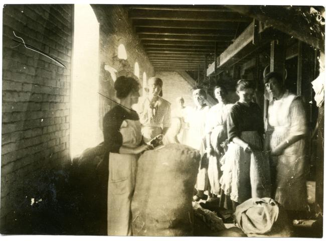 Unpacking and sorting clothing at warehouse in Alexandrowsk, Russia, in 1923, as part of MCC relief efforts. About 25 persons worked two weeks to unload this big shipment of six railway cars. Every bale was unpacked--the contents sorted and repacked.