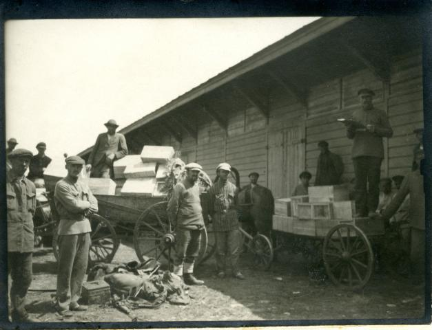 A relief distribution scene in Platovka, Russia. Mennonites pose with carts loaded with boxes of milk from MCC.
