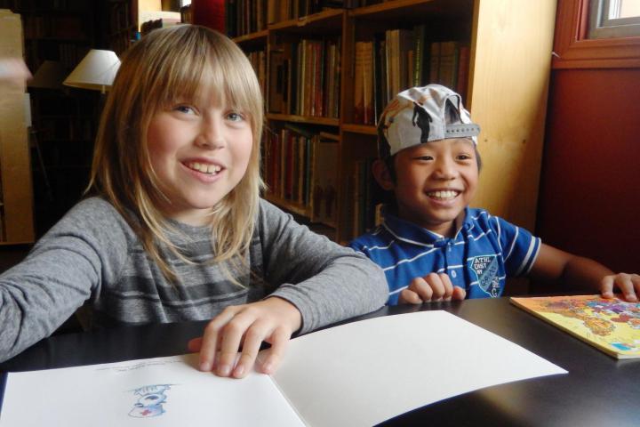 Lucien van de Laar and Carlos Salimbuat share a laugh over a book.