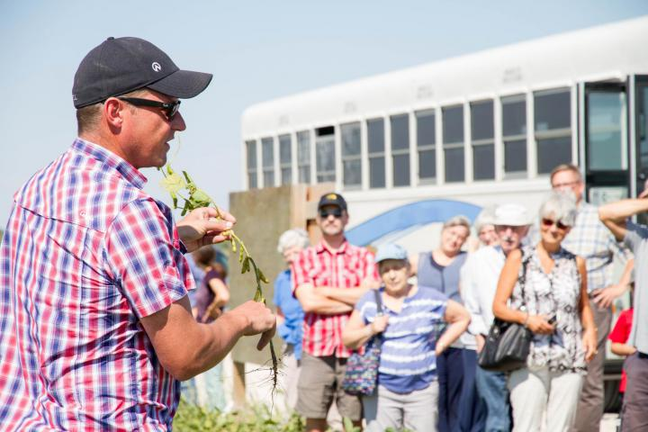 Farmer Grant Dyckexplains the growing cycle of soybeans to Grow Hope partners at the Harvest Celebration.