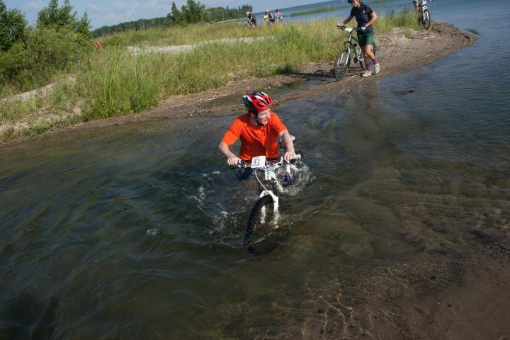 Mark Lysack pushes his bike through a wet section of the trail.
