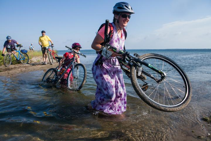 Tirzah Maendel carries her bike over a wet section of the trail.