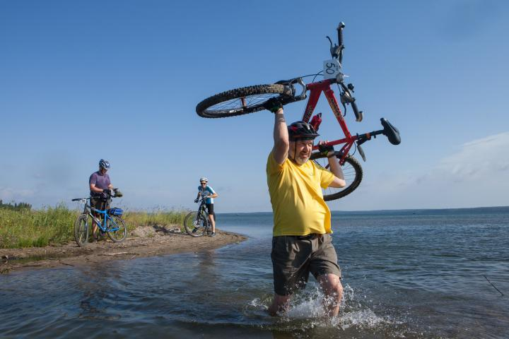 Greg Dimler carries his bike over a wet section of the trail.