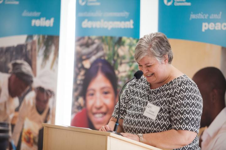 Catherine Enns, board chairperson of MCC Manitoba, welcomes guests to the Grow Hope harvest celebration at Crystal Spring Hutterite Colony on August 26, 2018.