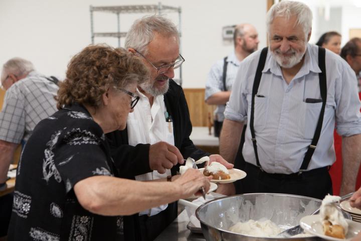 Edward Kleinsasser (centre) serves dessert to a harvest celebration guest.
