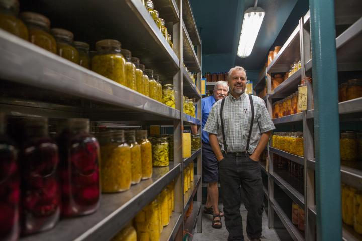 Victor Kleinsasser (front) leads 2018 harvest celebration guests on a tour of the pantry at Crystal Spring. Guest Martin Dueck follows.