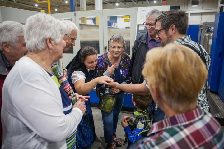 Guests examine a miniature bicycle laser cut from a sheet of steel during a guided tour of Silverwinds' fabrication shop at the 2019 harvest celebration.