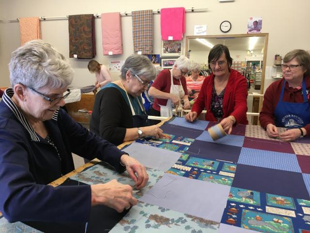 Volunteers at the Altona MCC Thrift Shop tie comforters on January 18, 2020 for the Great Winter Warm-up in Manitoba.