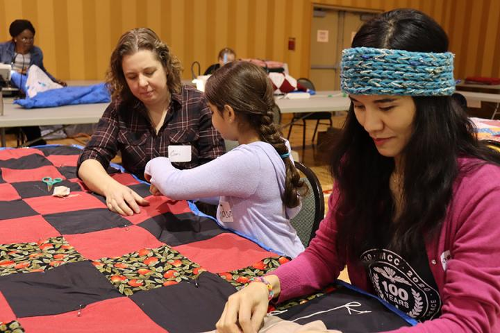 Corinne Narine (left) and her daughter Jaden tying their first comforter of the day withTing Terrazas (right) at the Great Winter Warm-up event at North Kildonan MB Church in Winnipeg on January 18, 2020.