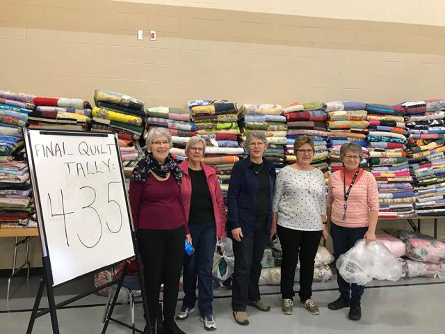 Hard-working volunteers Susie Harder, Mary Martens, Alvie Martens, Elenore Dyck, and Lois Janzen stand by the rows of comforters finished at the Great Winter Warm-up event in Steinbach on January 18, 2020.