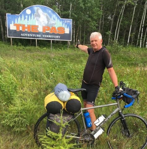Gerald Warkentin standing with his bike surrounded by grass in front of The Pas's welcome sign. The sign reads: The Pas Adventure Territory