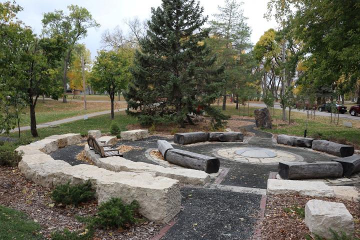 A circle of logs and stone surrounding a stone fireplace. Trees and an open grass park are in the background.