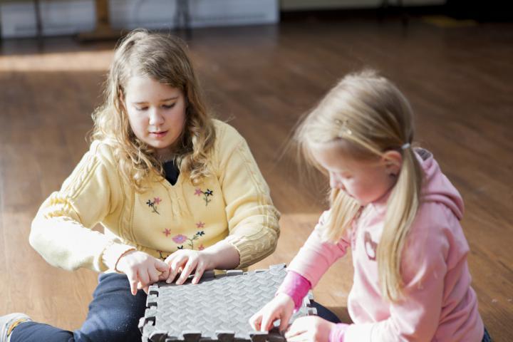 Two girls play with foam blocks
