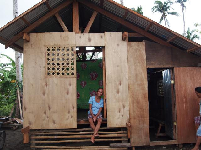 Dominga Arias in her new house built with a new shelter kit provided by MCC.