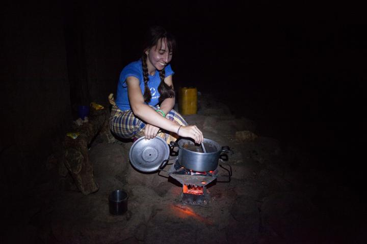 Rebecca Standen prepares her evening meal outside her house in Mozambique