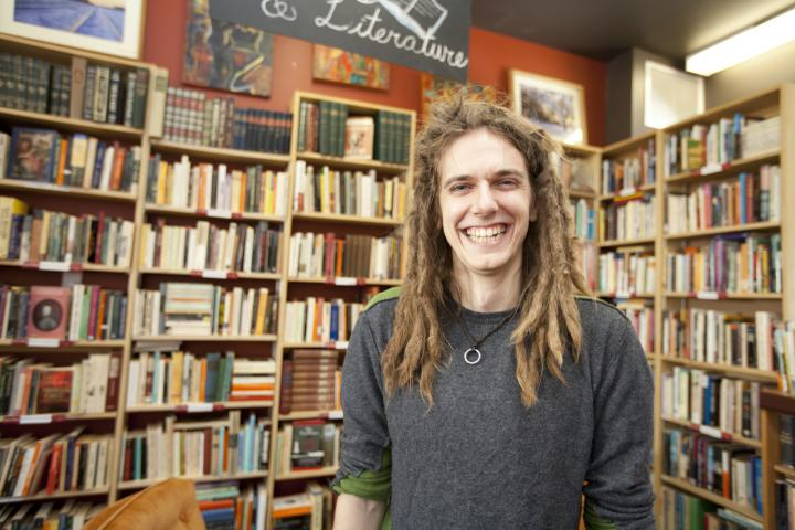 manager Andy Arthur in front of bookshelves at Sam's Place