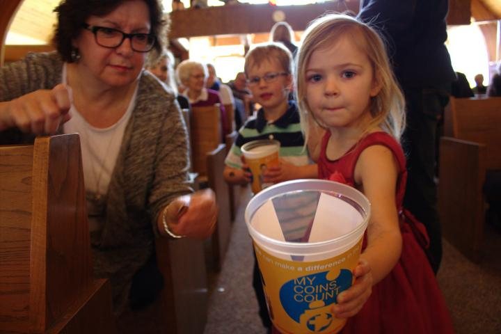 Roxanne Klassen puts a few coins in Eliana Rempel's bucket as Zachary Penner looks over her shoulder.