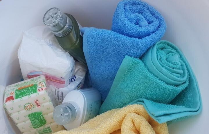 Plastic bucket filled with three towels, shampoo and soap.