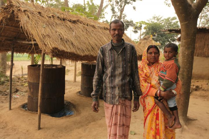 Bengali farmers Biren Mahato and Anzu Rani and their son Choton Mahato stand next to their trichocompost processing area. The compost reduces the reliance on costly fertilizer and increases the yield of their crops.