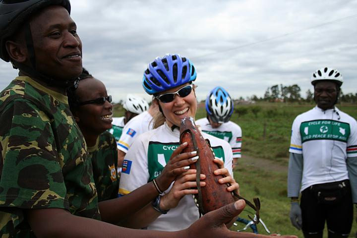 Canadian speed skater, Cindy Klassen (holding gourd) tries a traditional goat milk beverage and enjoys the friendship of other cyclists and supporters of the Cycle for Life tour, including (from left) Simon Macharia, Maureen Chepkemoi, and Samuel Nyongesa.