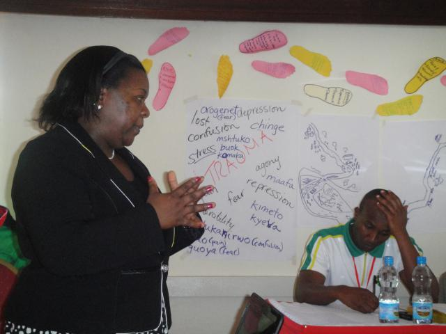 Doreen Ruto, director of Daima Initiatives for Peace and Development, leading a retreat for first responders, including participant Charles Mugo, on trauma healing after the attack on the Westgate mall in Nairobi, Kenya.