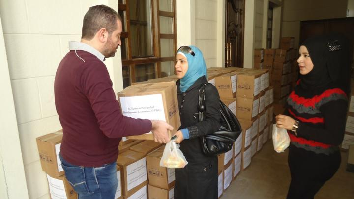 In Damascus, a woman accepts a box of food supplied by MCC through its partner, the Syrian Orthodox Church. She is not identified for security reasons.