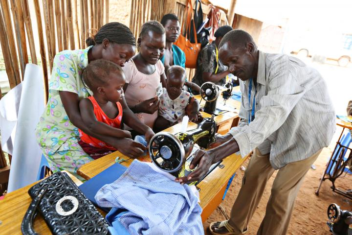 Toddlers Ester Keji and Emmanuel Kenyi watch while their mothers Jerisa Muro and Hellen Poni talk with tailoring instructor Mustafa Atrima.