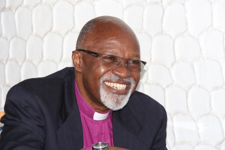 Un homme portant un collier clérical sourit