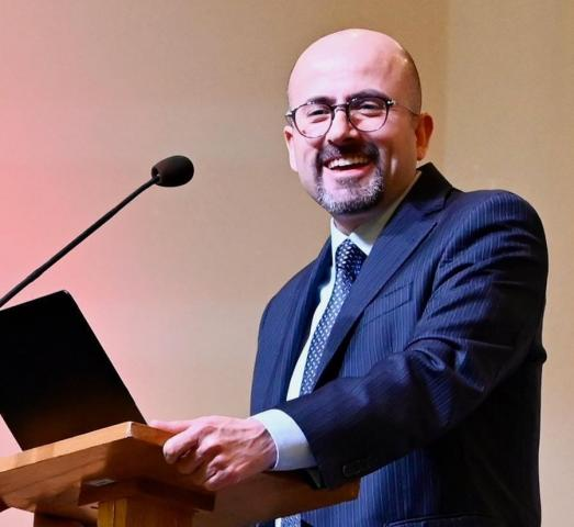 A man with a beard wearing glasses, a navy blue suit and navy blue tie with a white shirt, stands at a small wooden podium with a microphone in front of him. He looks to his left towards the camera and smiles.