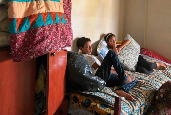 A teenage boy and girl sit on a bed with a quilt hanging on the cupobard next to them