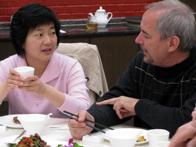 Two people seated at a table sharing dinner