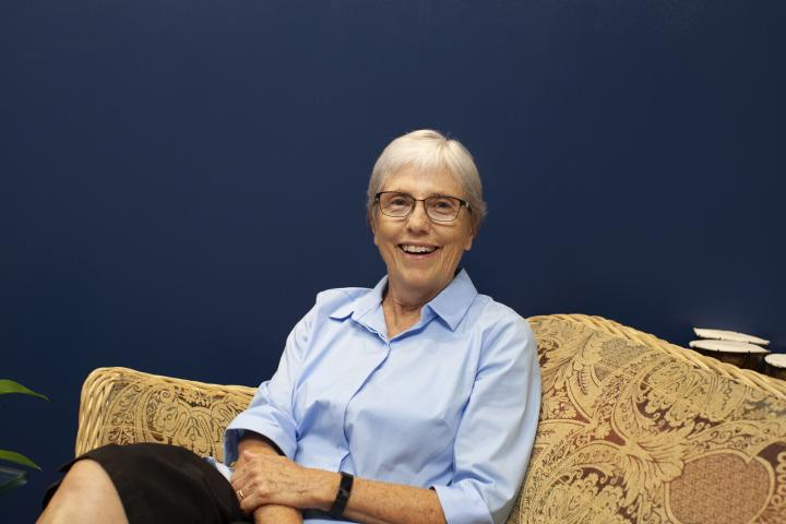 A smiling woman with glasses and short silver hair, wearing a blue collared button up shirt, sits on a couch and looks to her left into the camera.