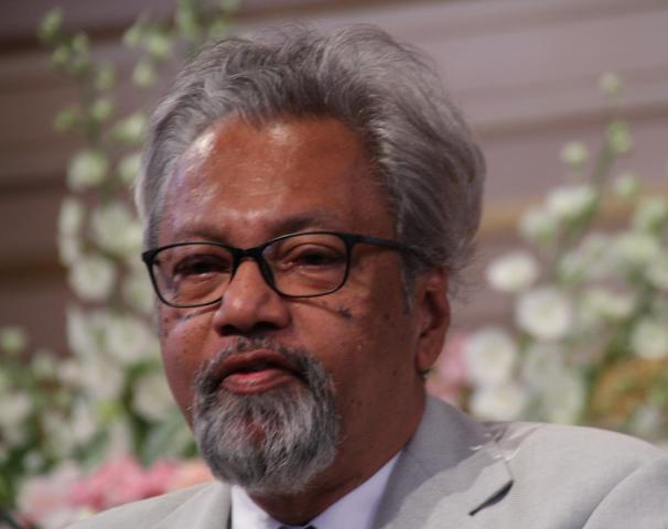 Close up of a man with silver hair and a beard wearing glasses and a grey suit jacket.